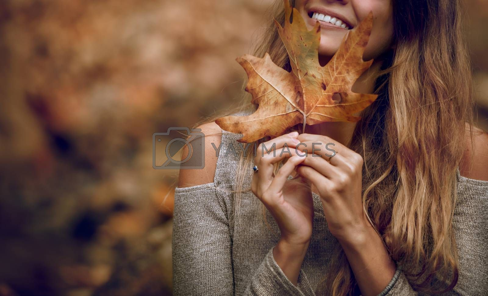 Connected to Nature Beautiful Young Model Posing in Autumnal Park. Covering Face with Dry Maple Leaf. Beauty of Autumn Season.