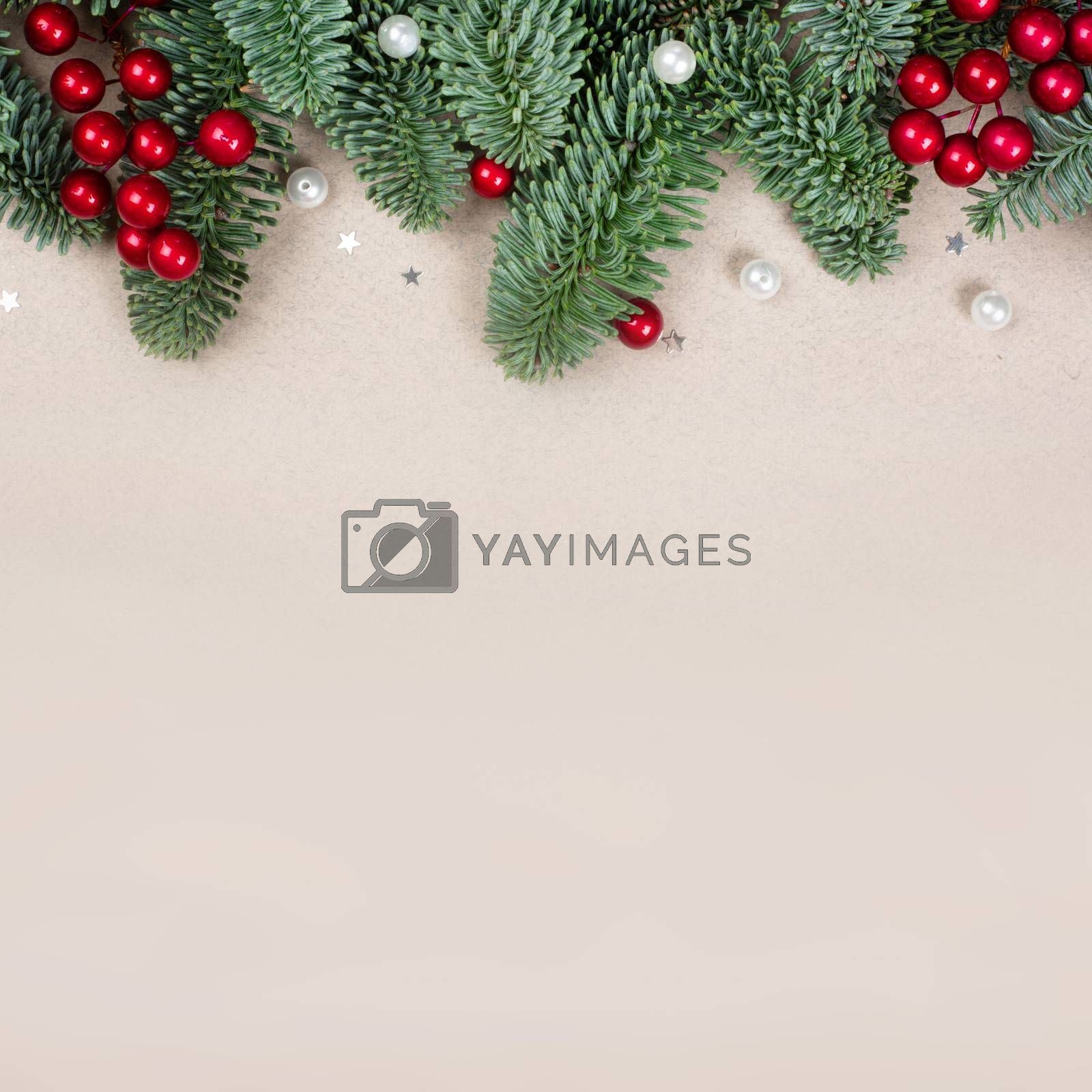 Traditional green christmas tree noble fir baubles berries and small decor border frame on craft paper background copy space for text