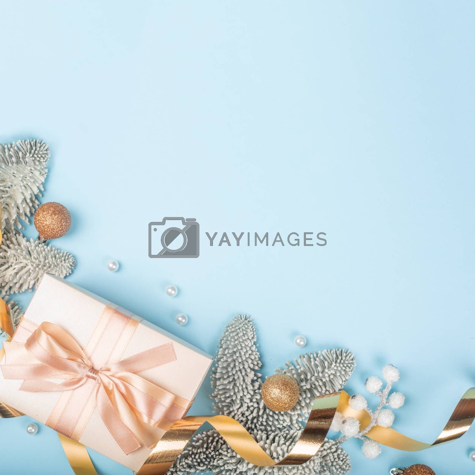 Frosted fir tree twigs and Christmas golden decorative bauble balls and gift box on blue background with copy space for text template flat lay top view design
