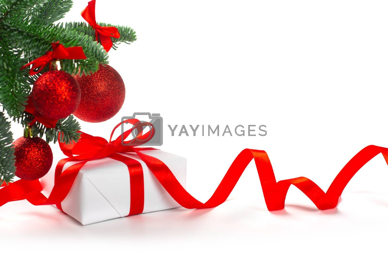 White holiday present gift box with red satin bow and curly ribbon under Christmas tree with baubles, border frame design isolated on white background