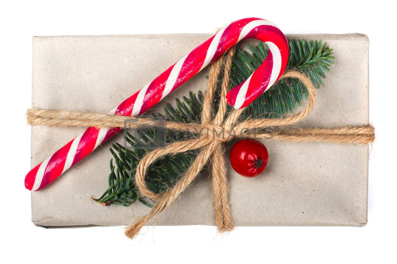 Wrapped vintage christmas gift box in craft paper with rope bow, striped candy cane fir tree twig and red berry isolated on white