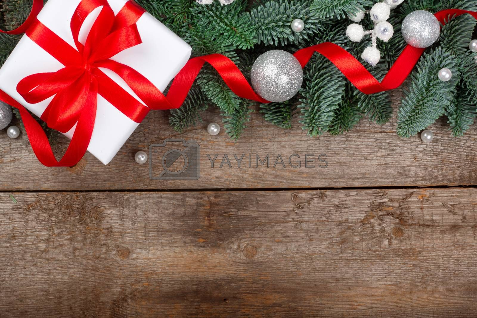 Christmas gift fir tree branches with festive decoration on wooden background