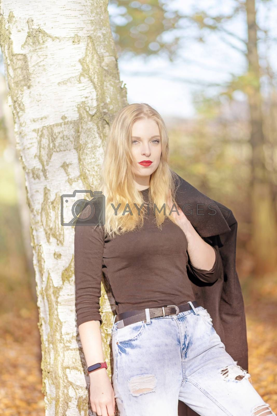 Portrait of attractive girl leaning on a tree trunk in autumn park. The girl is looking at the camera. Photo in soft light autumn colors.