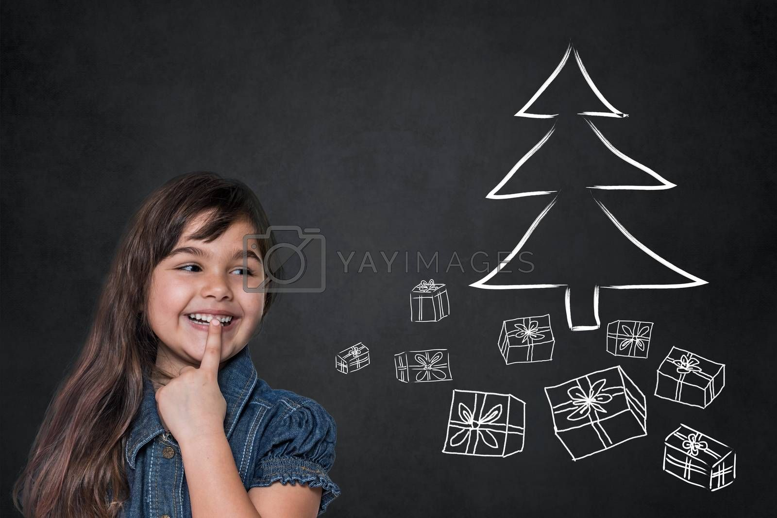 Smiling tanned long haired little girl is looking at  drawn Christmas tree and packages on a black chalkboard