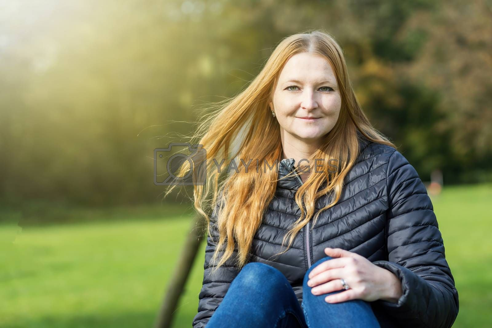 Portrait of red haired young woman posing n autumn park. The woman is looking at the camera.