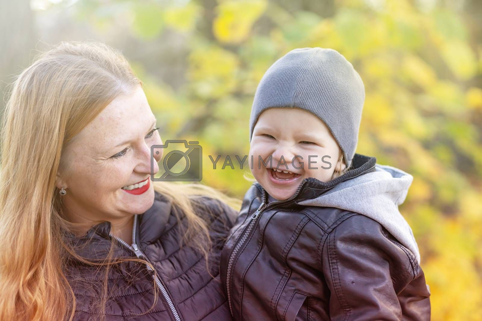 Laughing red haired mother with her little son are posing in autumn park closeup.