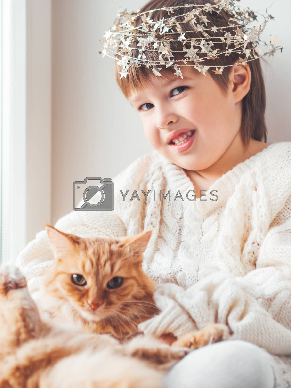 Kid with decorative star tinsel for Christmas tree hugs cute ginger cat. Boy in cable knit oversized sweater with fluffy pet. Winter holiday spirit. New year.