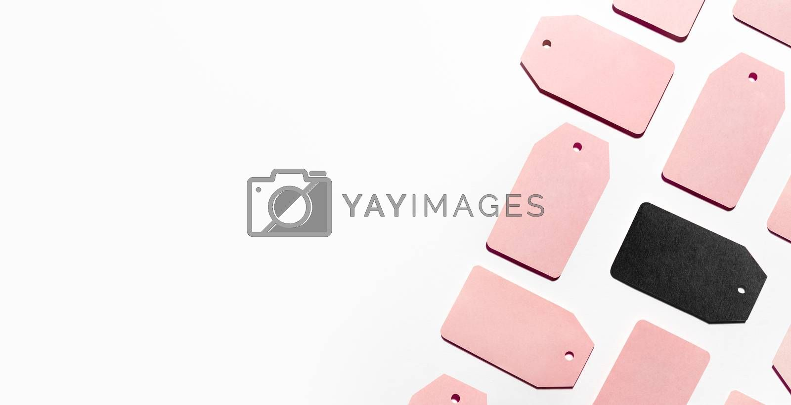 Top view on pattern of many pink and one black clothes tags on white background. Glamorous labels with copy space. Symbol of black Friday sale and shopping. Flat lay.