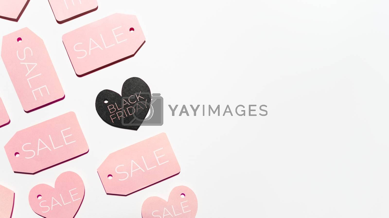 Top view on pattern of pink and black clothes tags in shape of heart on white background. Glamorous labels with copy space. Symbol of black Friday sale and shopping. Flat lay.