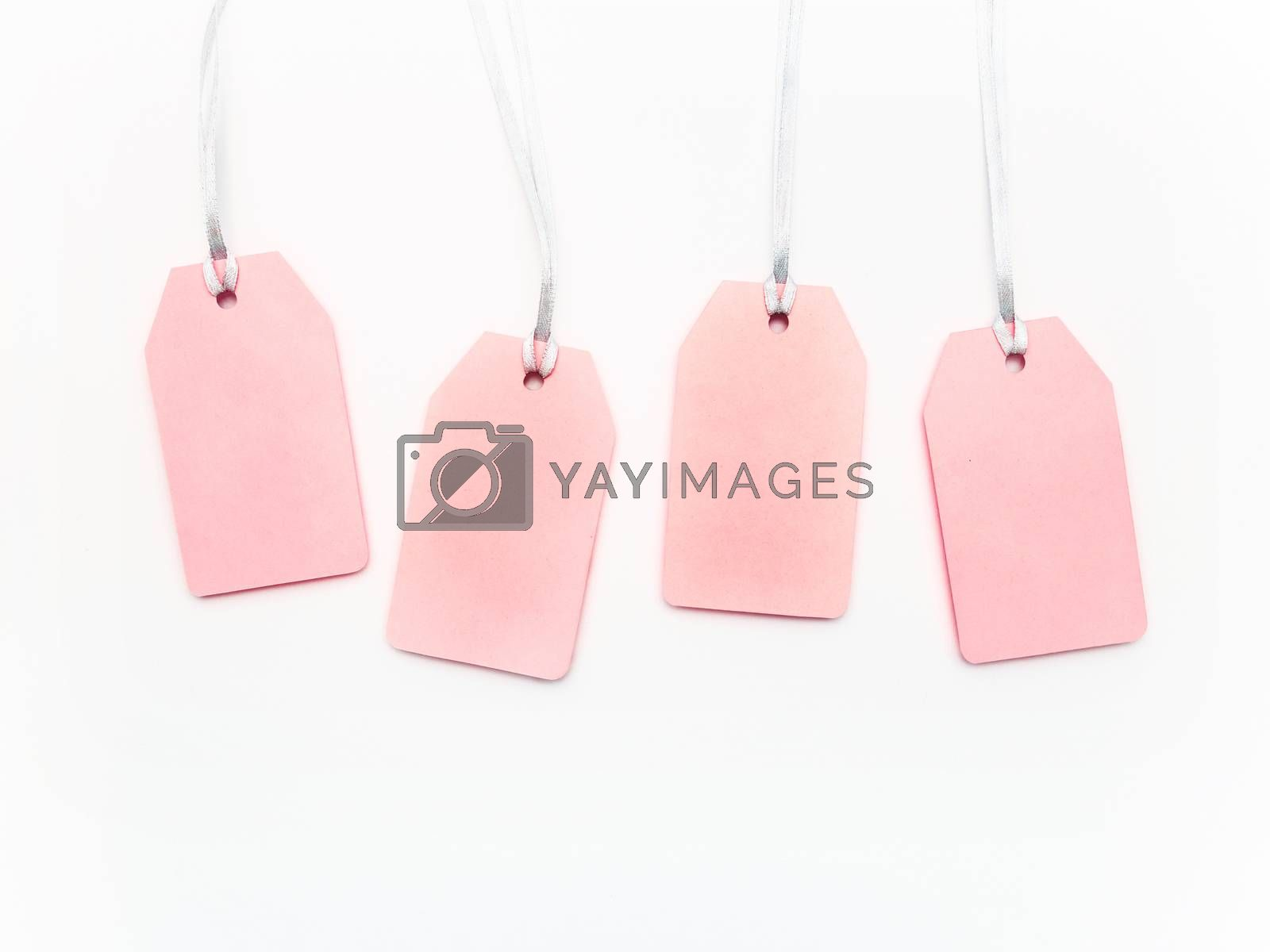 Four pink clear tags on white background. Glamorous labels on silver threads with copy space. Symbol of sale and shopping. Top view, flat lay.