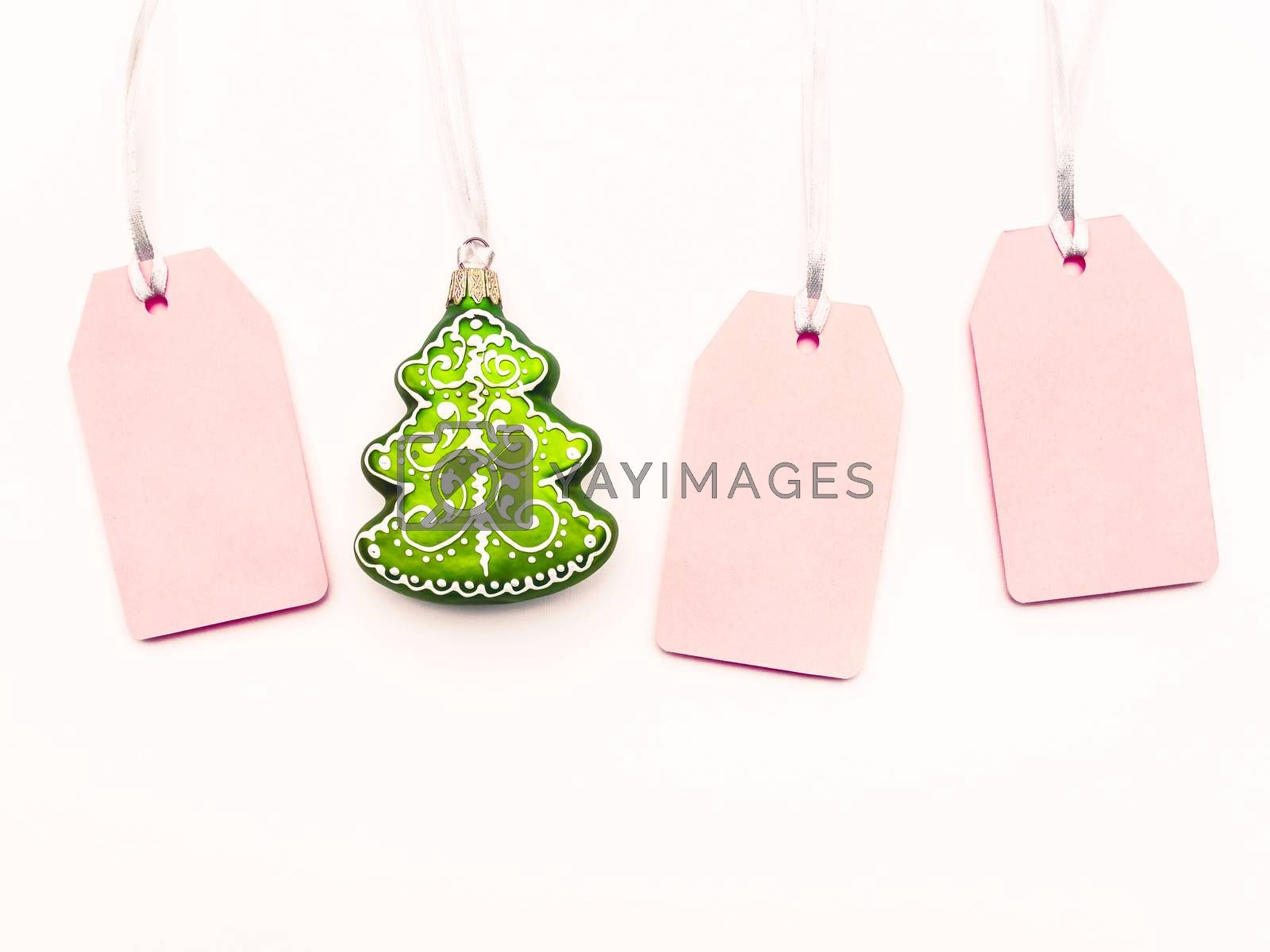 Three pink clear tags and decorative Chrsitmas tree on white background. Glamorous labels on silver threads with copy space. New Year symbol of sale and shopping. Top view, flat lay.