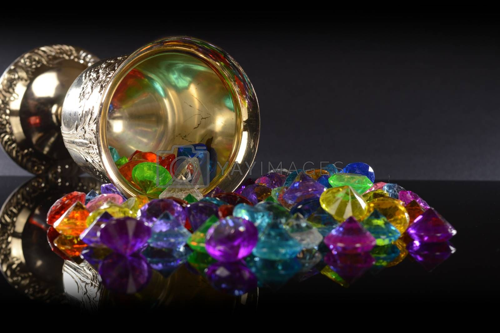 A closeup view of some treasured gemstones and a silver wineglass over a black reflective background.