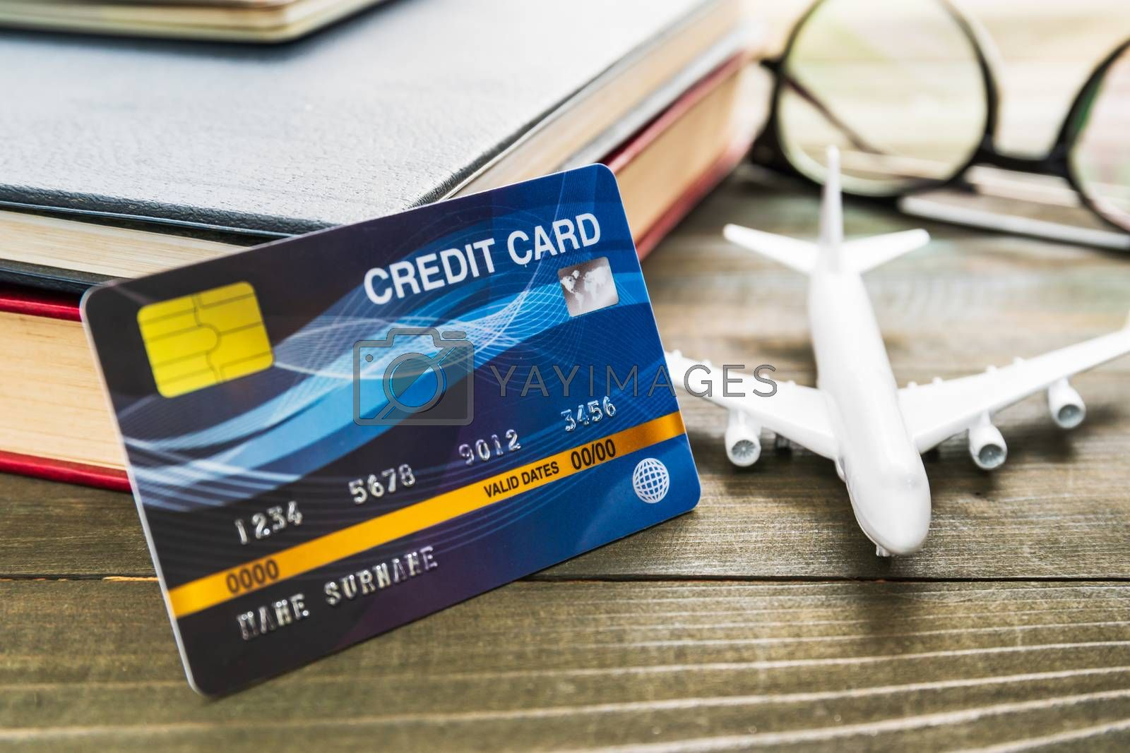 Credit card and airplane model on wooden table , Preparation for Traveling concept
