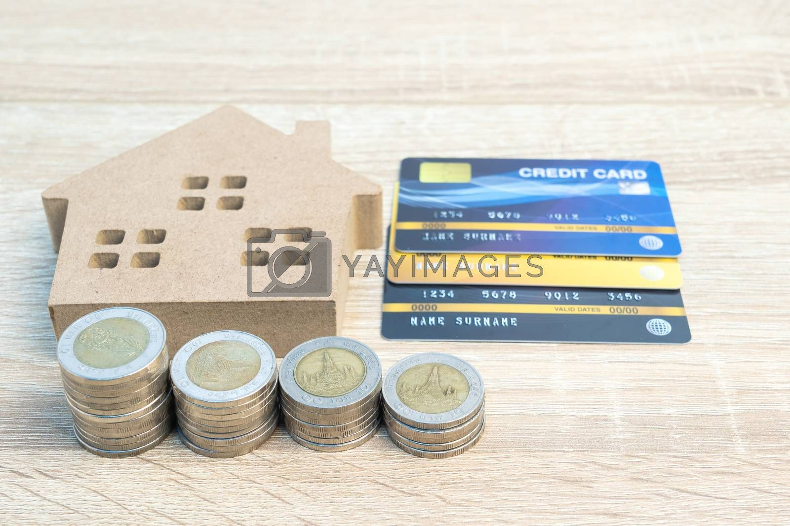 House model and coins with credit card on wood table using as property real estate and financial concept