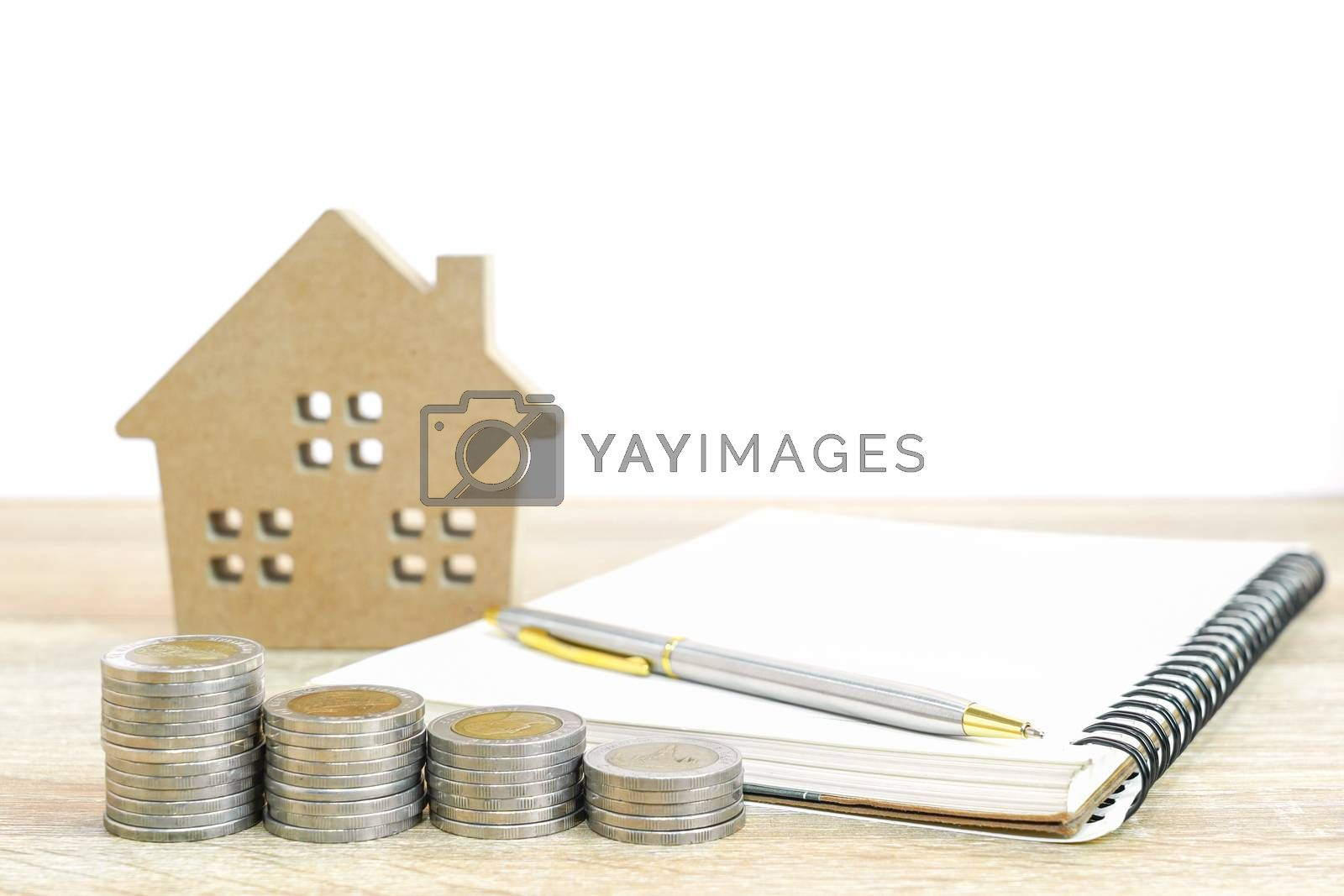House model and notepad with coins on table for finance and banking concept