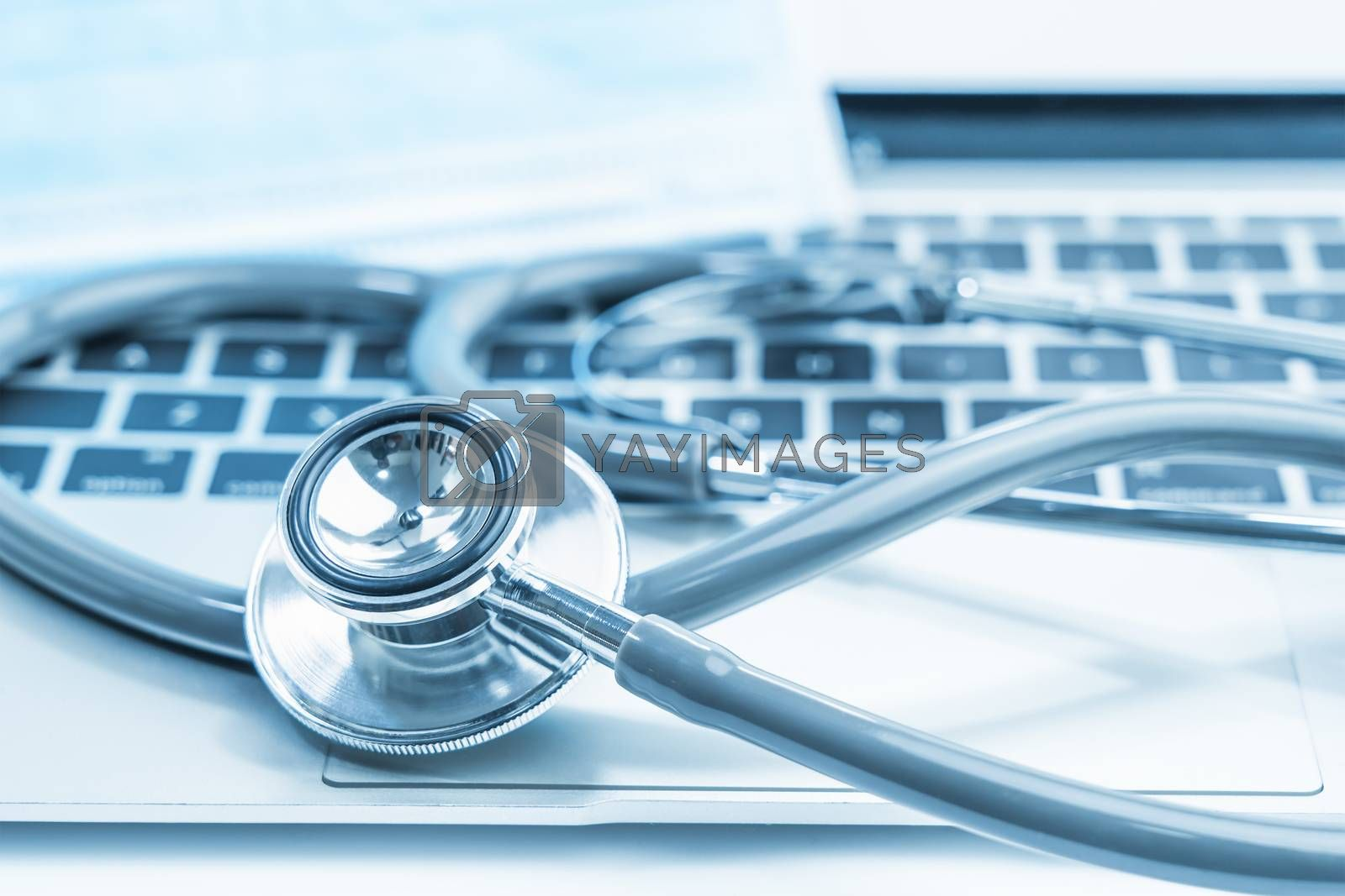 Medical stethoscope for doctor checkup on laptop with medical face masks as medical concept
