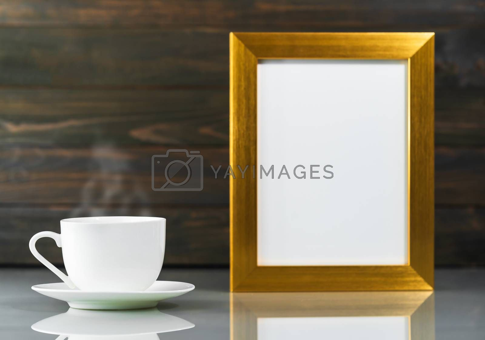 Picture mock up with golden frame and coffee cup over table with wood wall background