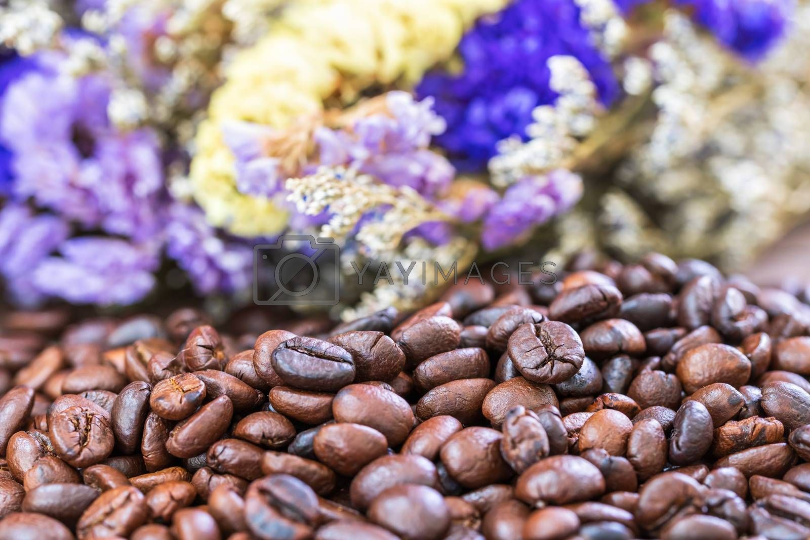 Close up roasted coffee beans heap with flower background