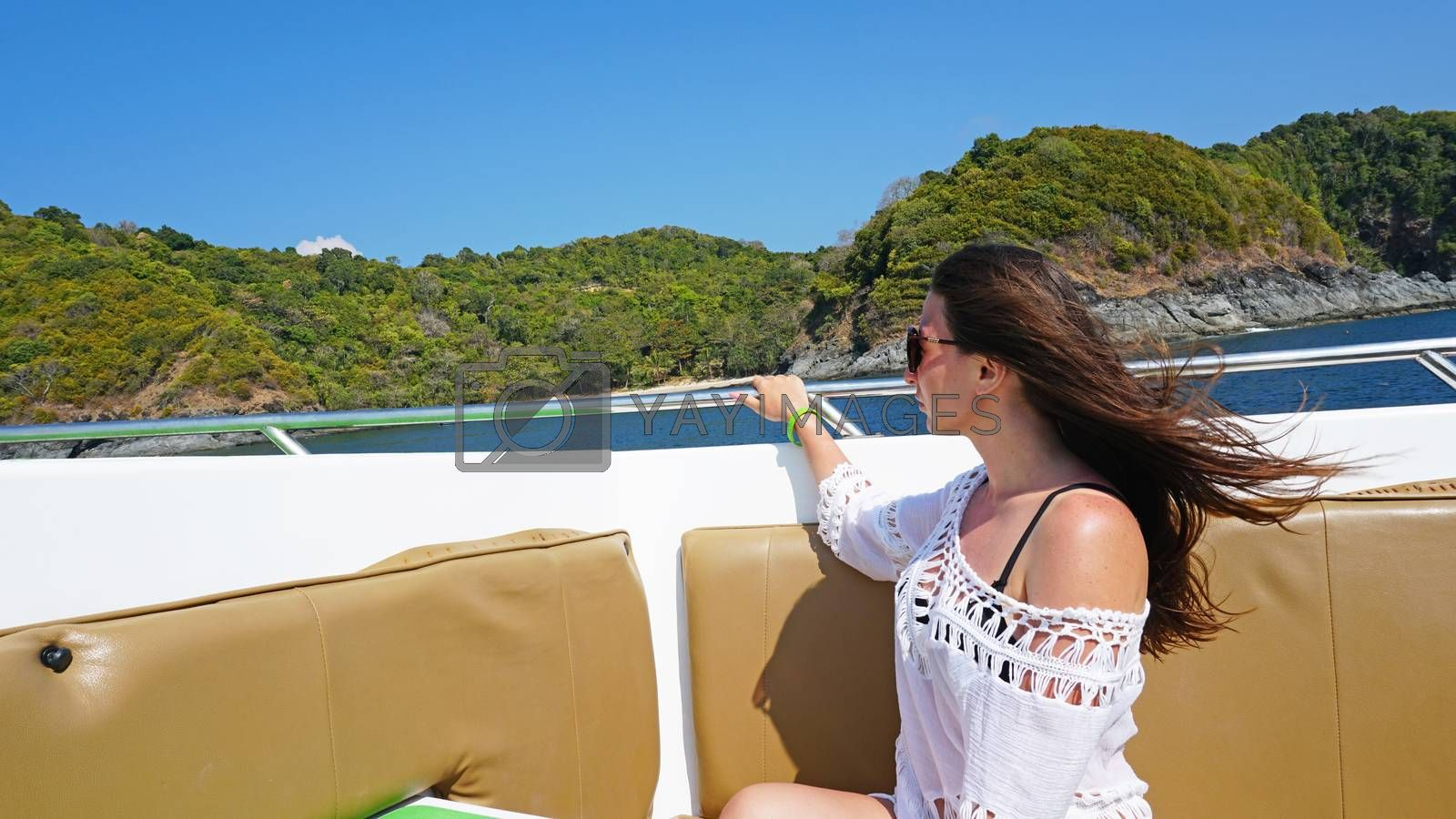 Girl sitting on the nose of the speedboat. Hair fluttering in the wind, glasses in front of his eyes. White robe. View of green island and blue sea. Shoulder's open. Comfortable leather seats.
