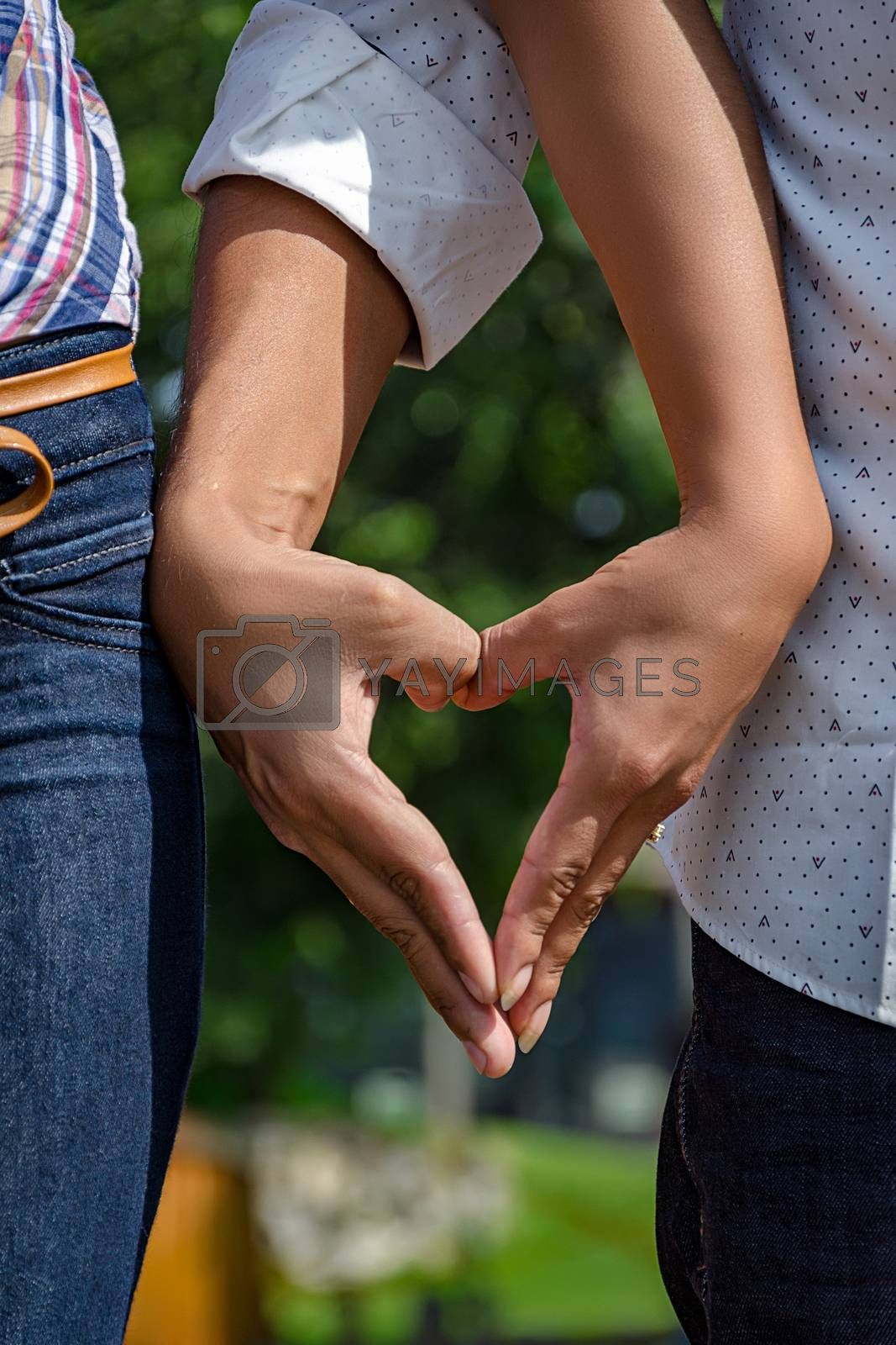 wedding couple holding hands in a heart shape, with the background of a park