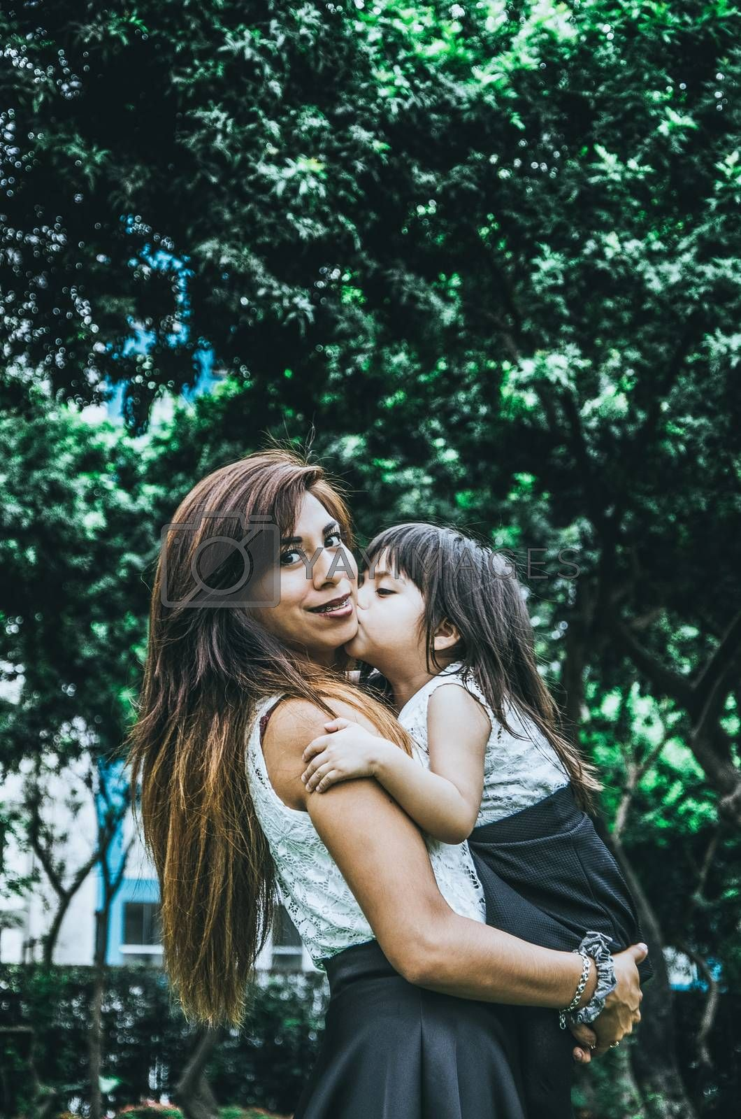 Happy Mother's Day. The little girl kisses her on the cheek
