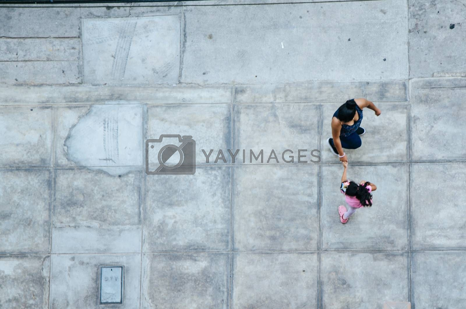 Mother and daughter walking on the pavement. View from above