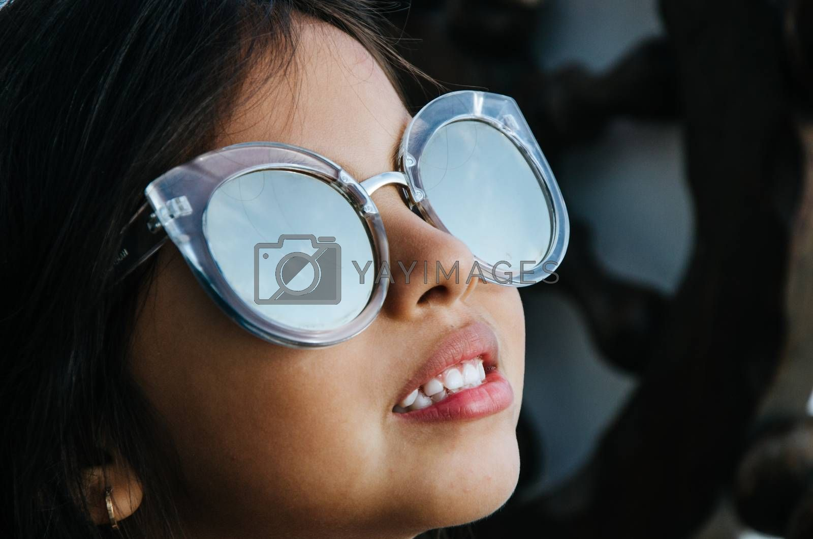 Cute little girl smiling with adult sun glasses