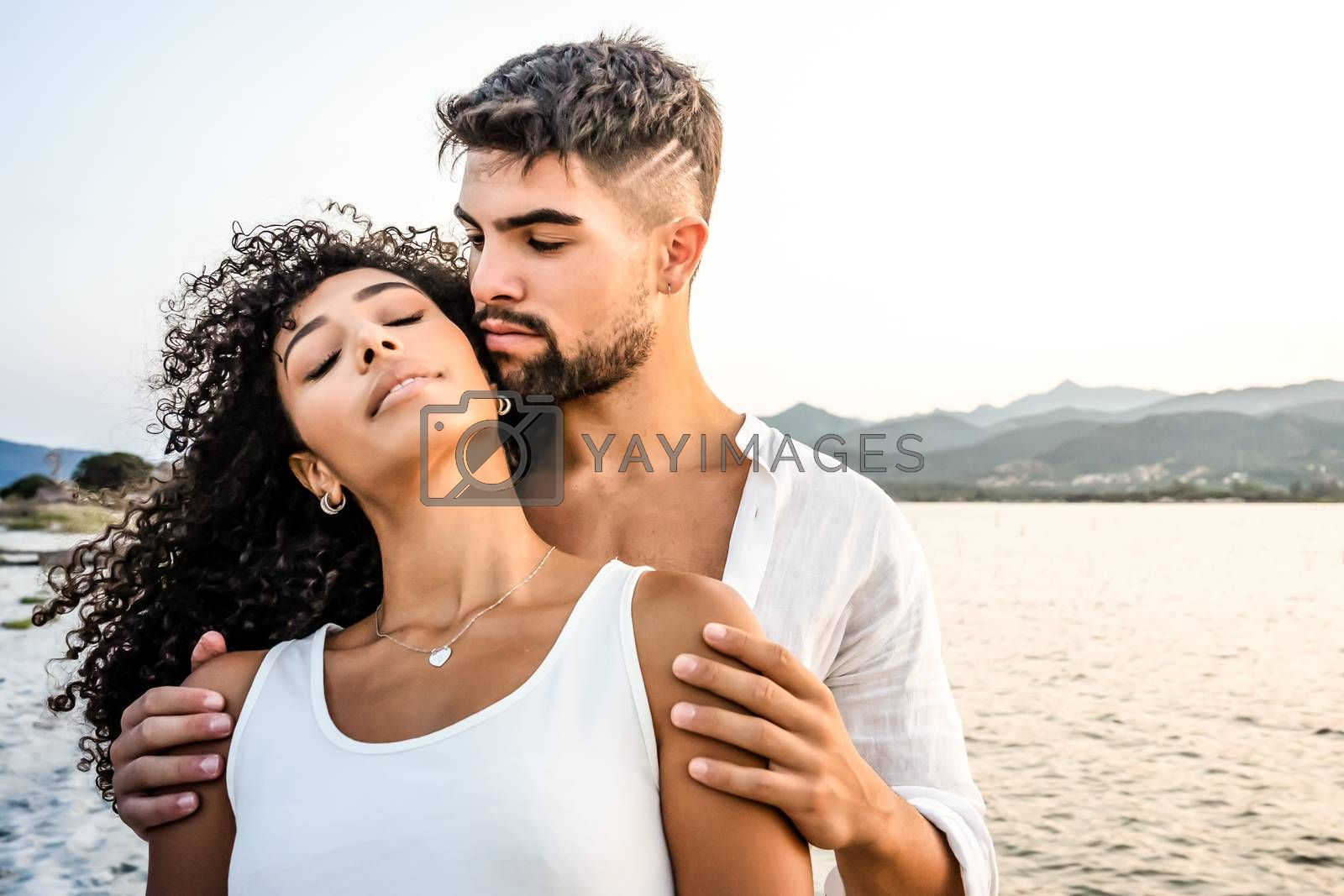 Royalty free image of Heterosexual mixed race couple in romance scene at sunset with vintage photo effect filter - Handsome Caucasian guy embracing from back his Hispanic girlfriend with closed eyes - Focus on curly hair by robbyfontanesi