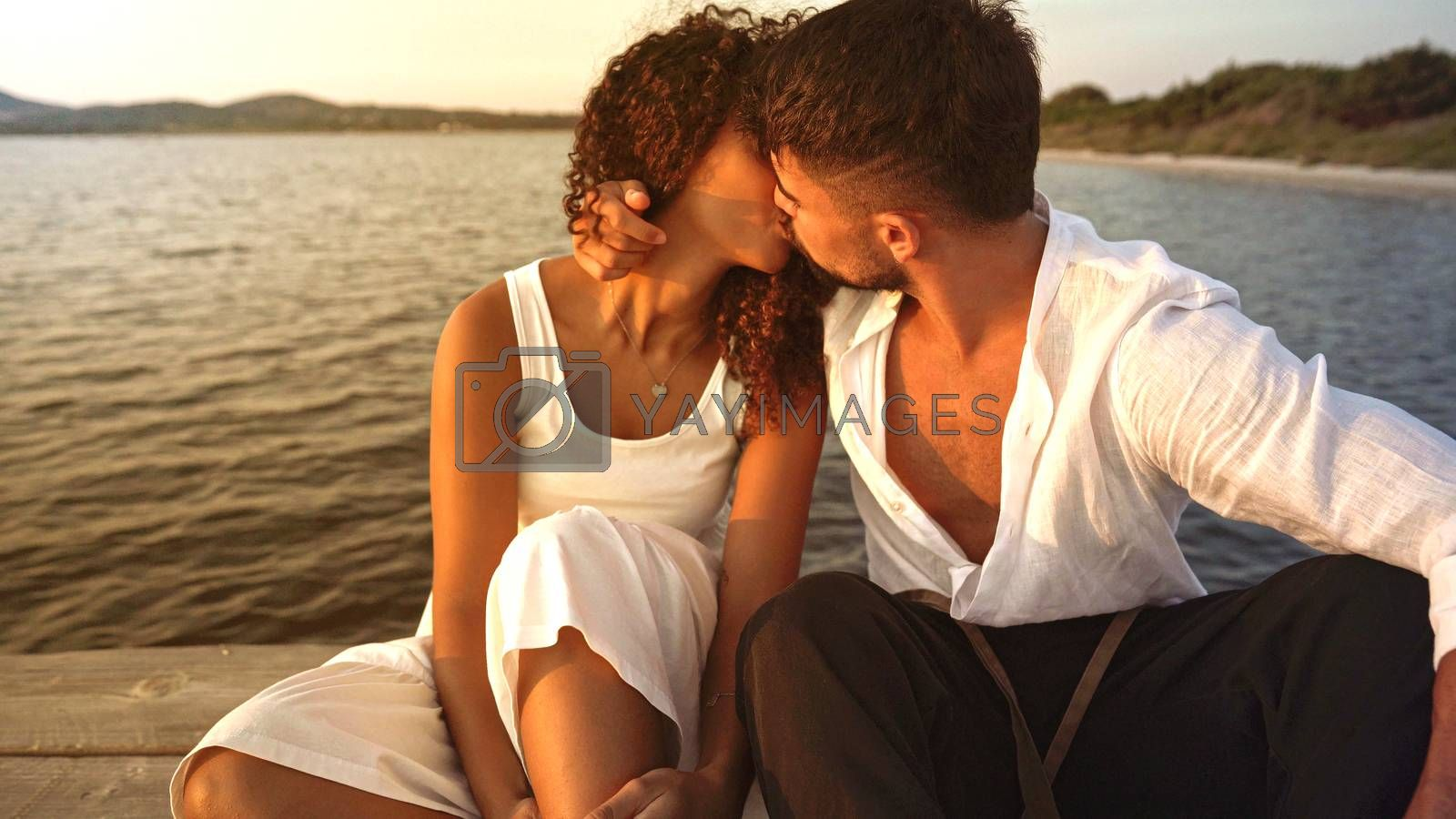 Romance scene of heterosexual mixed race couple of lovers kissing with passion on a wooden pier at sunset - Romantic handsome stylish young man flirting embracing her Hispanic curly girlfriend