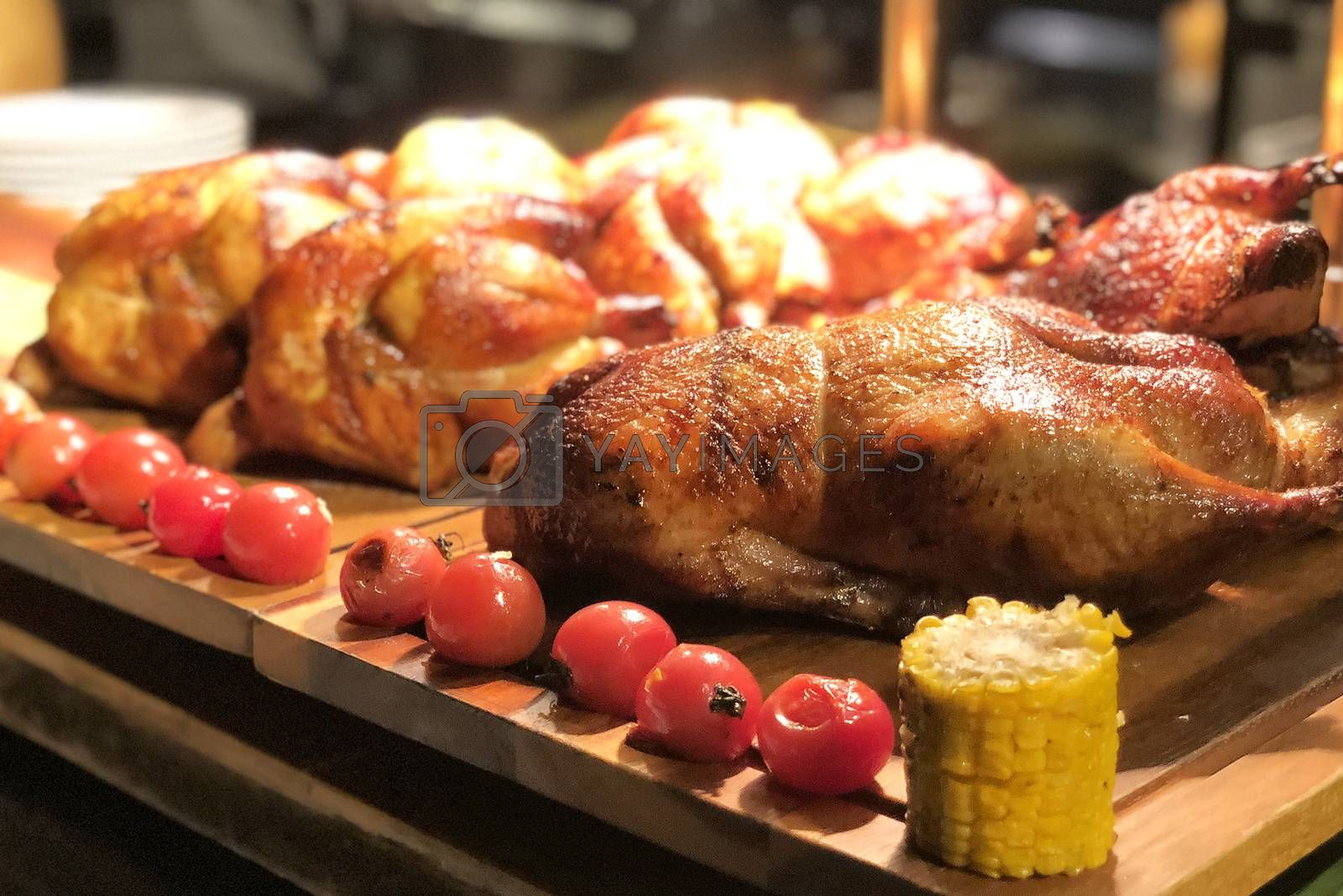 Roasted chicken with tomato and corn on wooden table