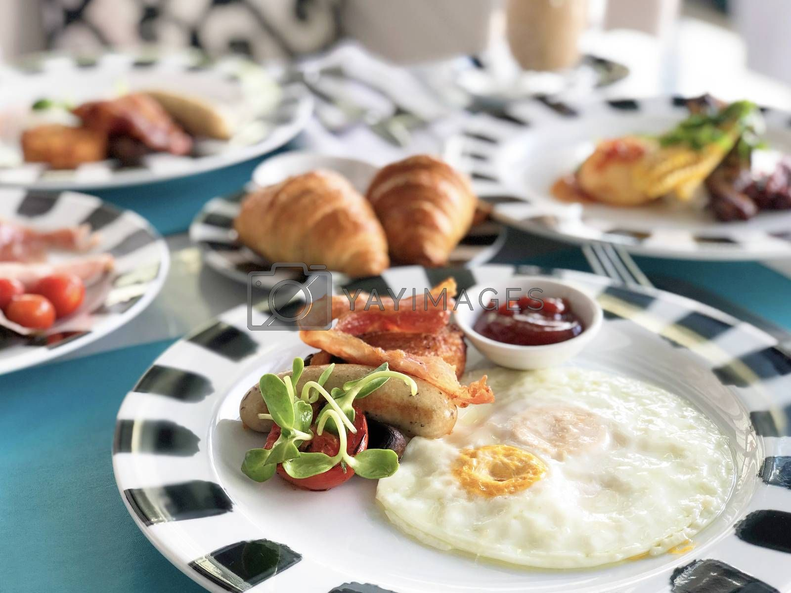 Delicious breakfast served with coffee, orange juice, egg, ham, bacon rolls at the luxury hotel