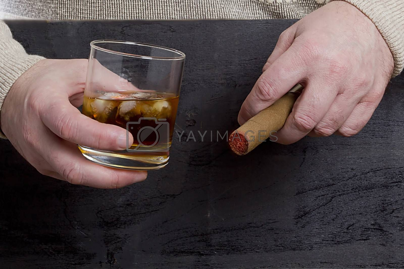 Men's hands with a cigar and a glass of whiskey