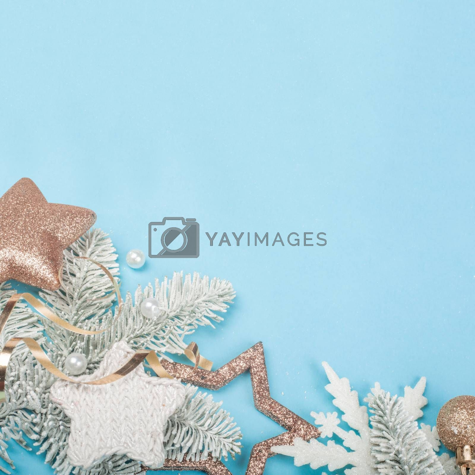Frosted fir tree twigs and Christmas decorative bauble balls on blue background with copy space for text template design