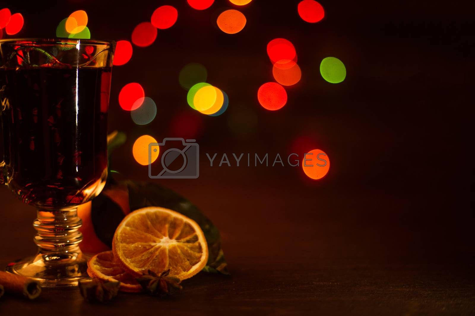 Mulled wine with cinnamon sticks and orange over holiday christmas lights background