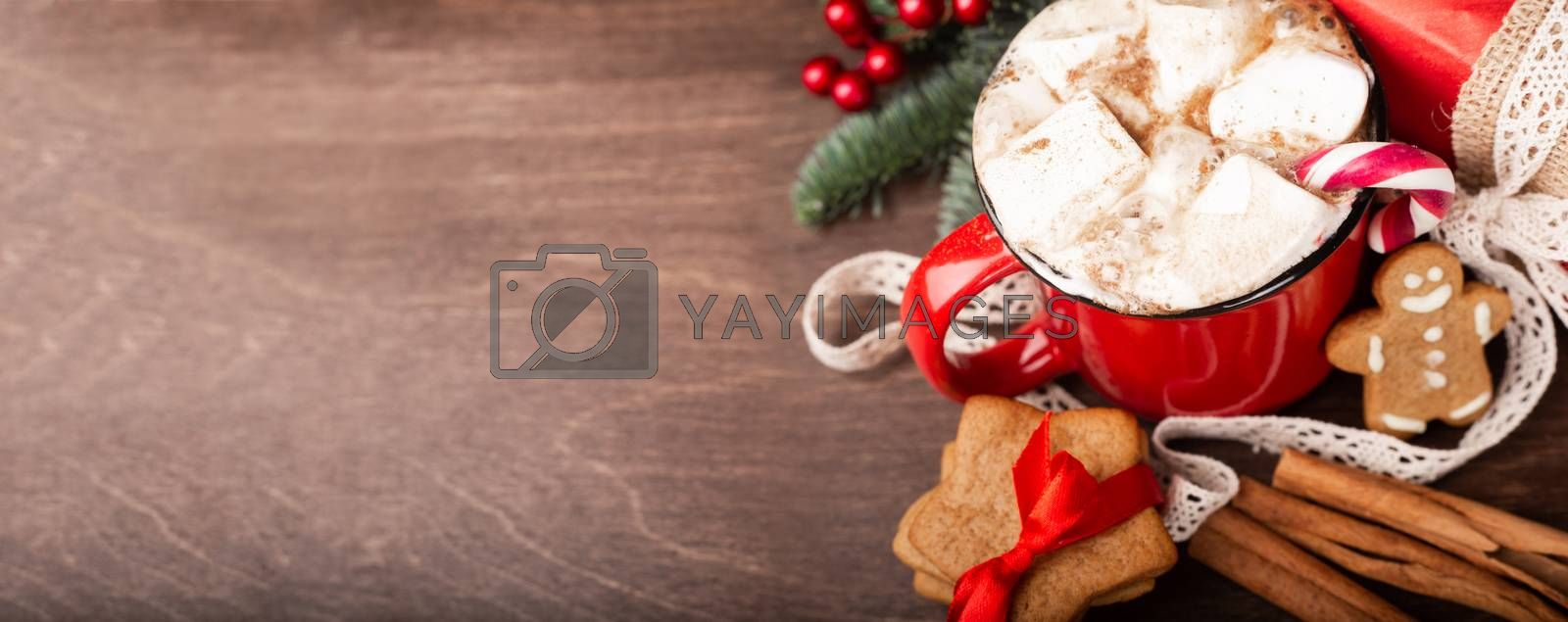 Cocoa in red mug with marshmallows candy cane fir tree branches and red baubles on dark wooden background with bokeh lights
