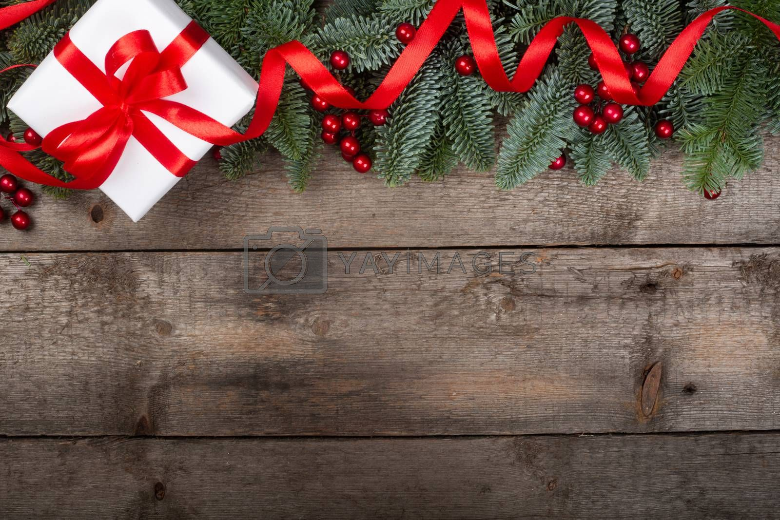 Christmas noble fir tree twigs and gift with red ribbon on wooden background with copy space for text