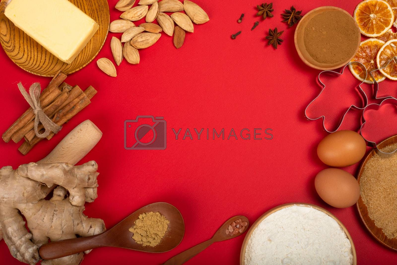 Christmas gingerbread cookies cooking background flat lay top view template with copy space for text. Baking utensils, spices and food ingredients on red paper