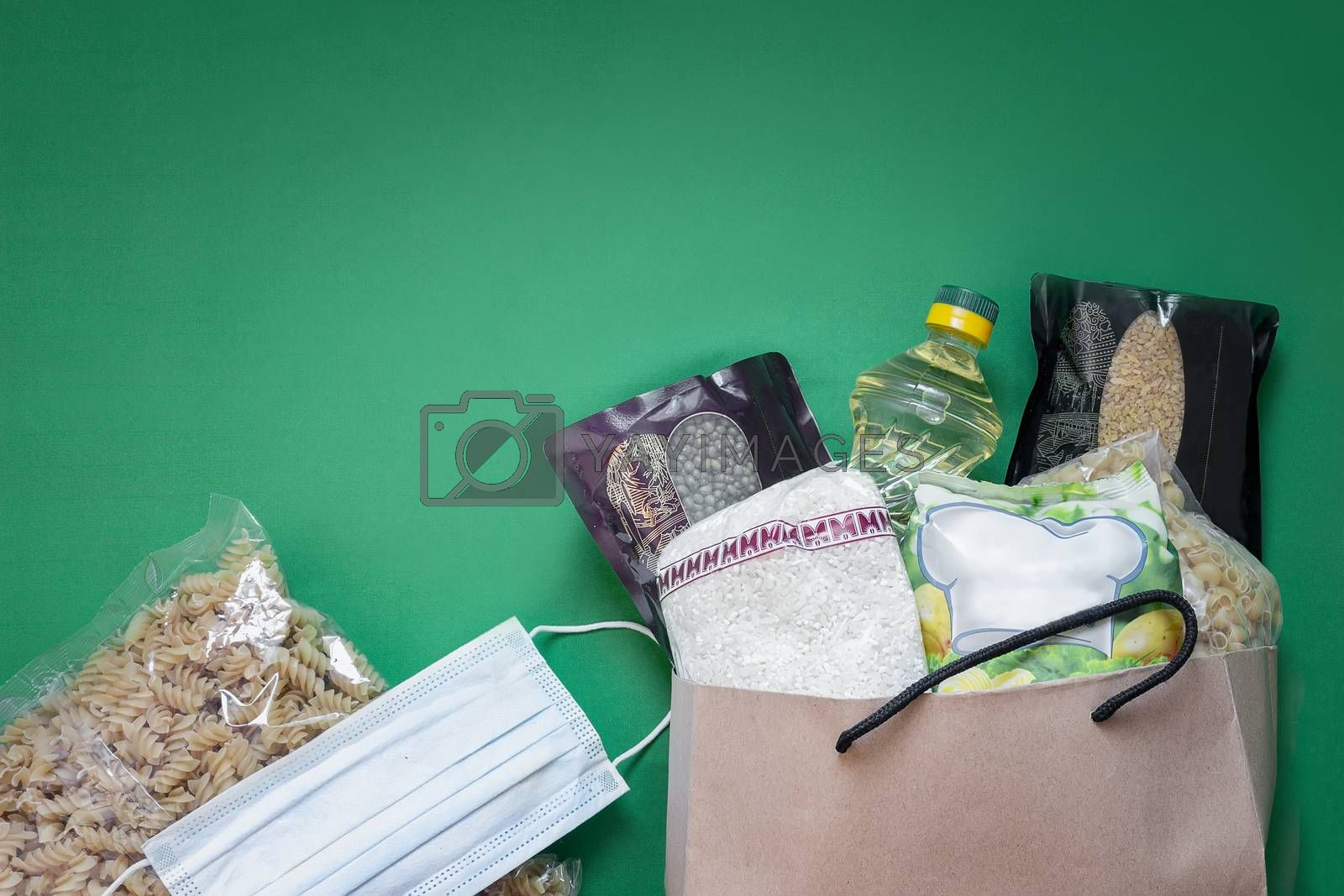 Crisis food supply for the period of quarantine isolation during the coronavirus pandemic. A set of products in a paper bag: rice, pasta, oatmeal, sugar, cereals. Food delivery. Top view, copy space