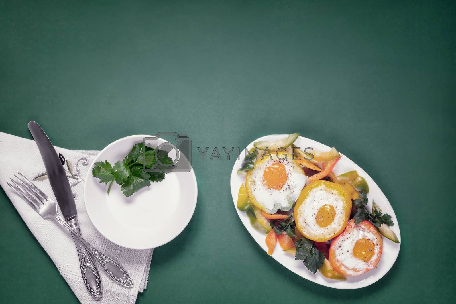 On the table on a plate are three oven-baked bell peppers with an egg inside each pepper. There is an empty plate next to it . Top view with copy space. Flat lay