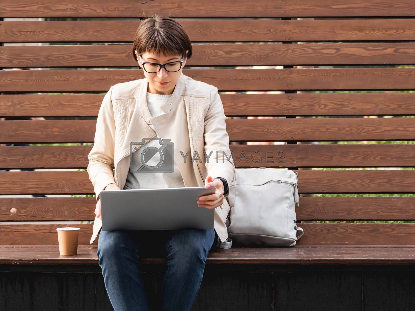 Business woman with short haircut and eyeglasses sits on wooden bench in park with laptop and cardboard cup of coffee. Student learns remotely from outdoors. Modern Internet technologies. Video call.