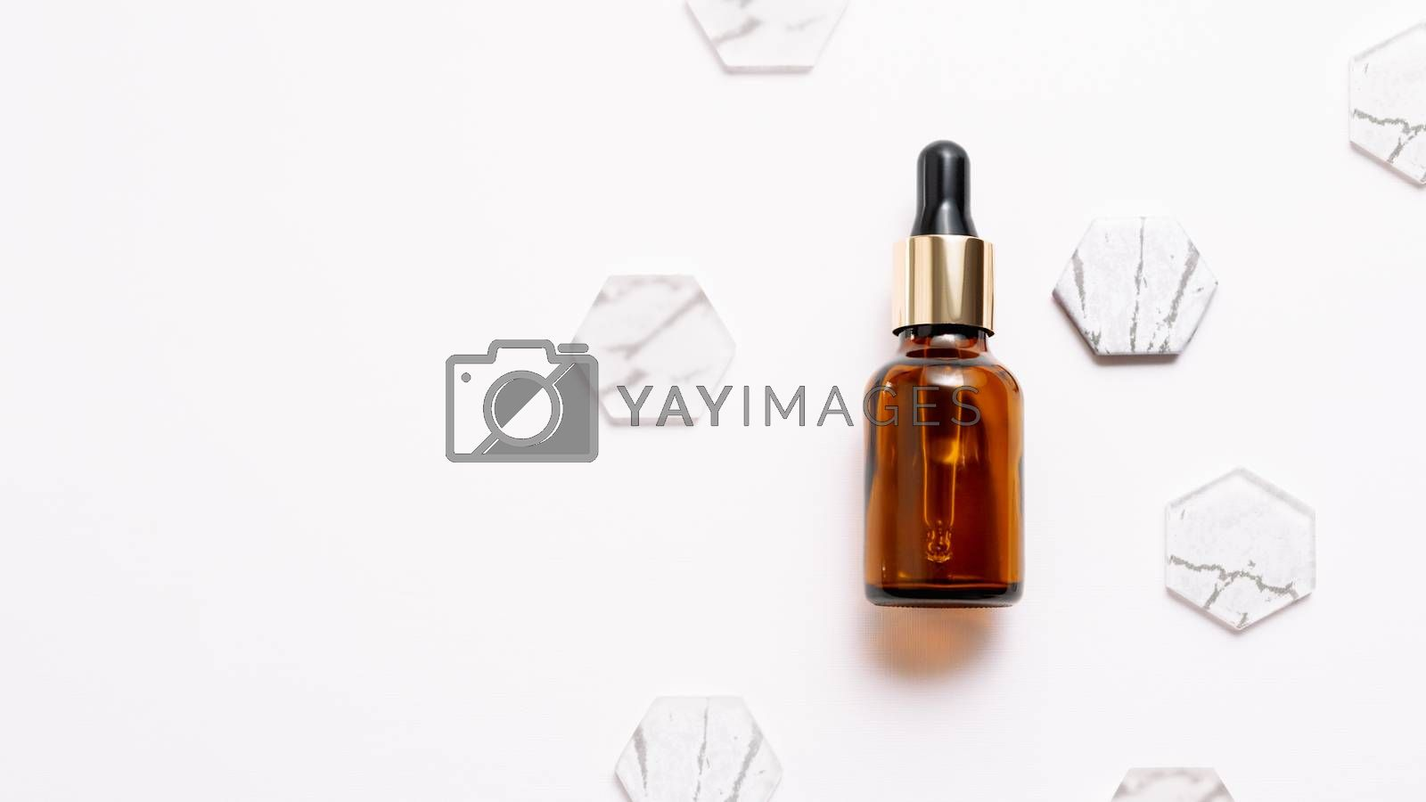 Top view on glass bottles of essential oil or cosmetic serum on white background. White copy space with decorative marble and glass hexagons.