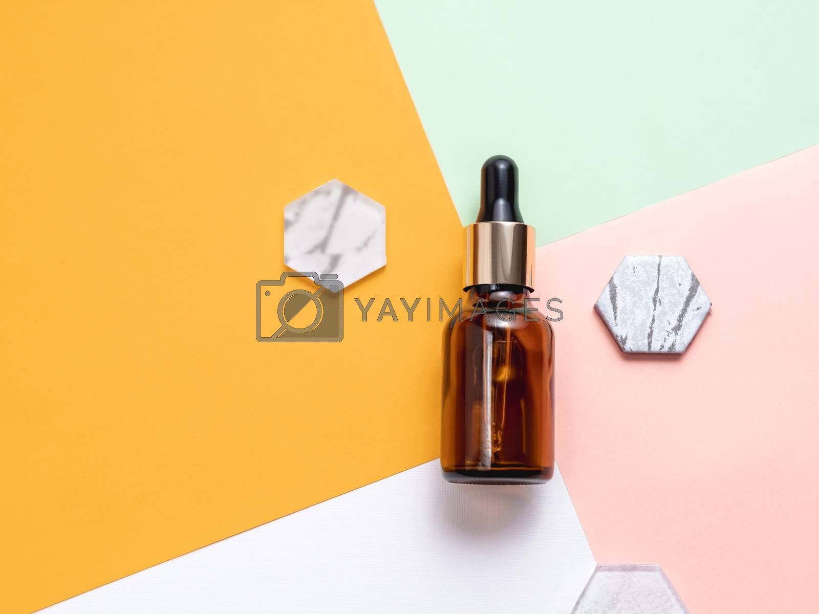Top view on glass bottles of essential oil or cosmetic serum on colorful geometrical background. Decorative marble and glass hexagons.