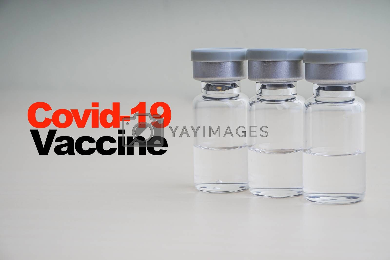 COVID -19 VACCINE text with vials on wooden background. Coronavirus or Covid-19 Vaccine concept