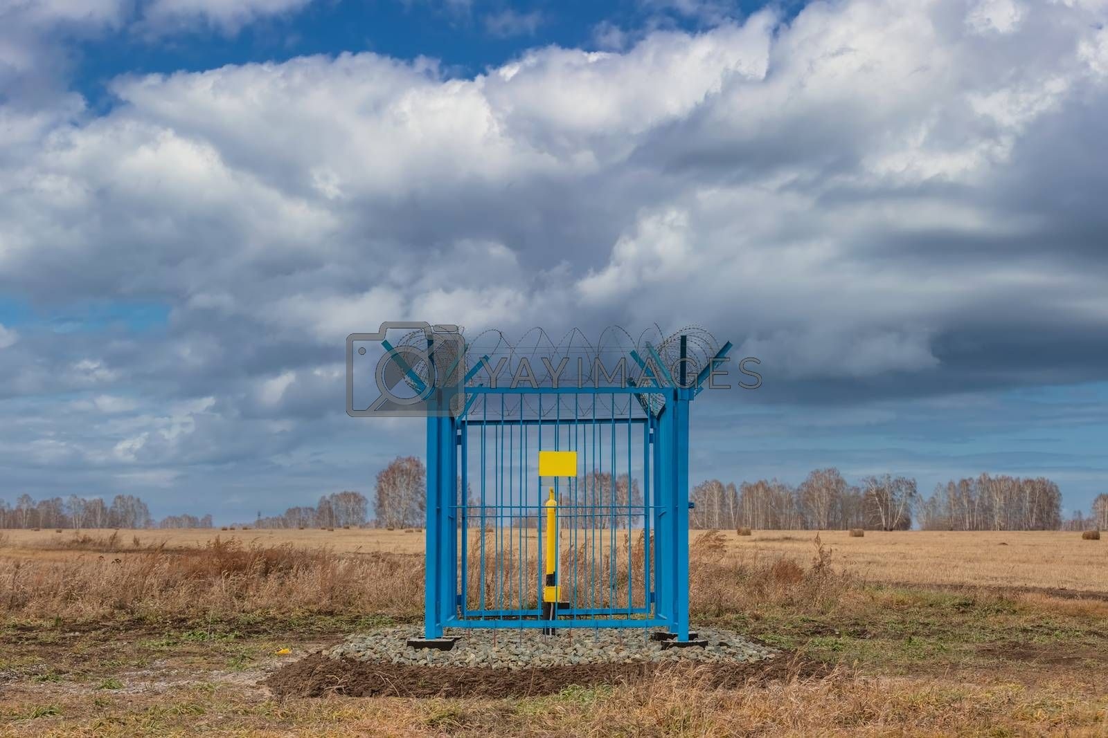 Shot of a caged industrial gas station with barbwire on top of the fence. Yellow gas pipe in the middle of the cage, empty yellow plate on the fence. Blue cloudy sky as a background. Siberia, Russia.
