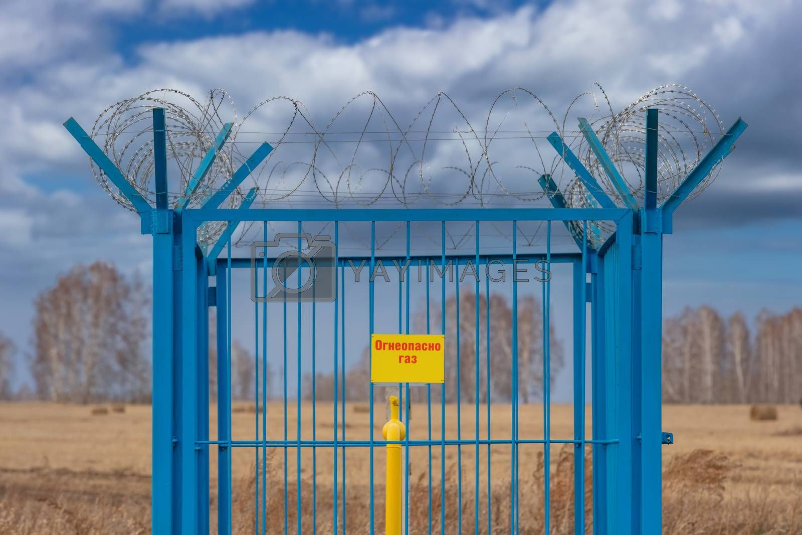 Shot of a caged industrial gas station with barbwire on top of the fence. Yellow gas pipe in the middle of the cage. Yellow plate on the fence reads in Russian - Flammable. Gas. Siberia, Russia.