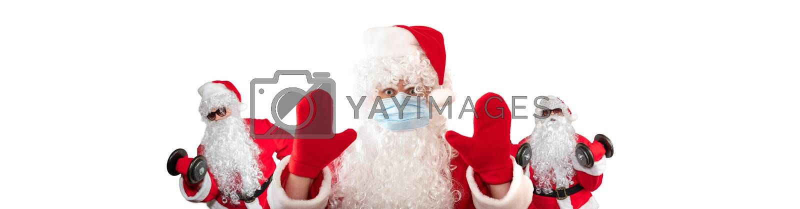 Santa Claus wearing a medical mask, having his both hands up, eyes wide open in warning gesture. Two Santa Clauses working out in the background behind him. Isolated on white background. Banner size, copy space.