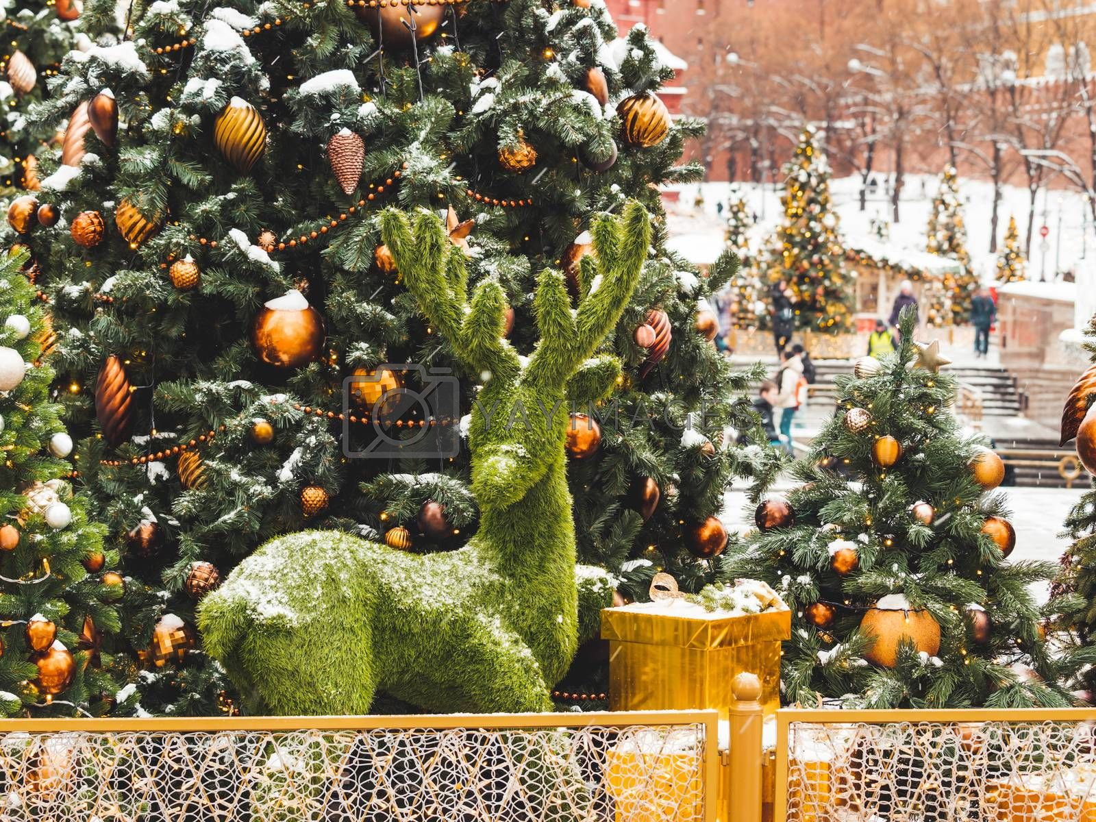 Christmas tree with golden and bronze balls and reindeer made of artificial grass. Outdoor decorations for New Year celebration. Moscow, Russia.