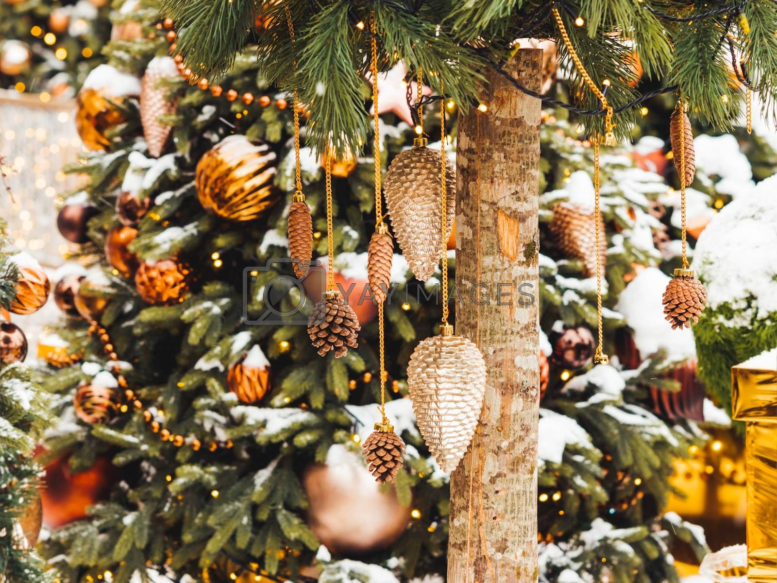 Christmas tree with golden and bronze decorations. Outdoor decorative pine cones and balls for New Year celebration.