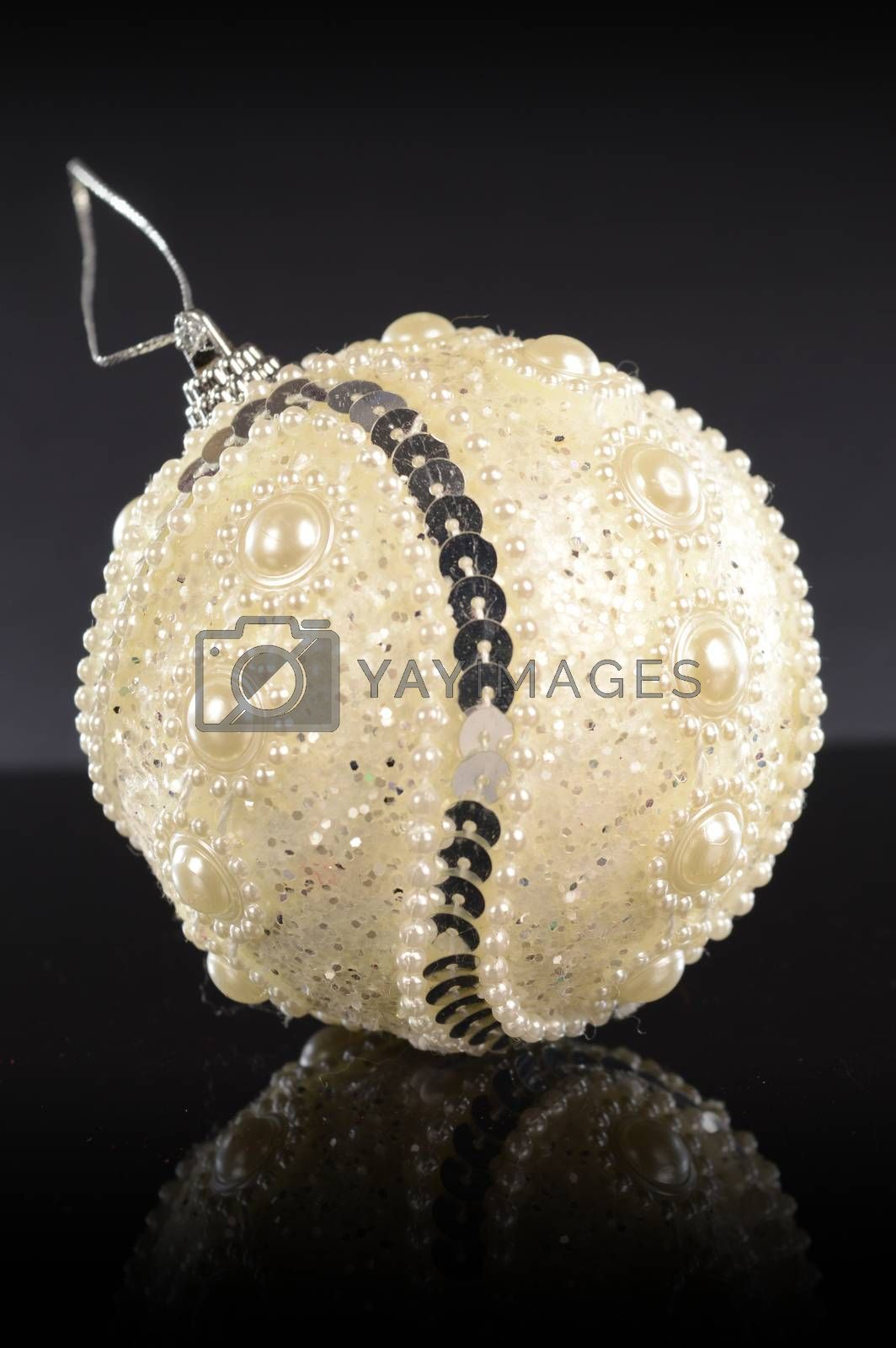 A closeup vertical composition of a white festive holiday bauble for tree decorating during the Christmas season.