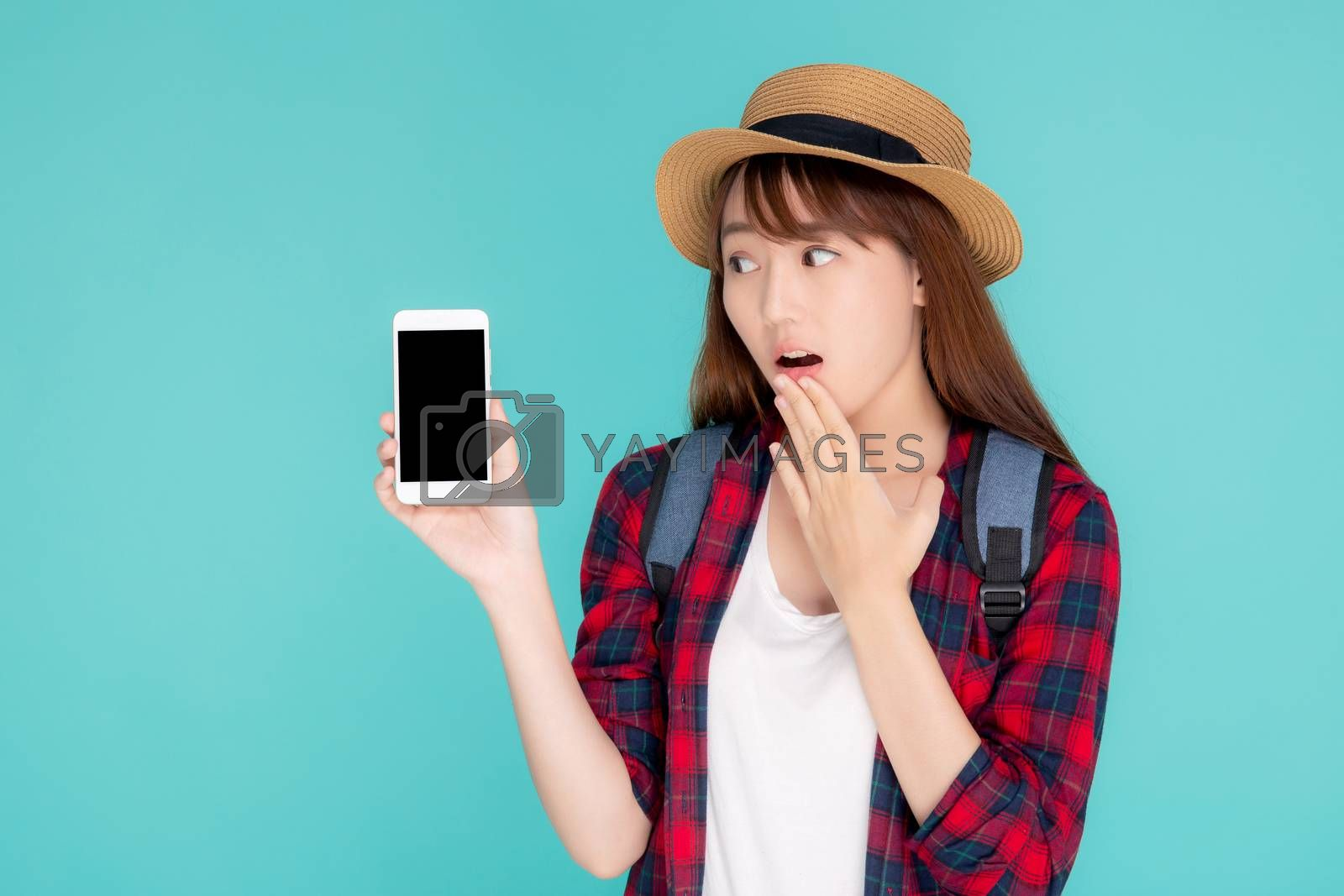 Beautiful young asian woman presenting and showing smart mobile phone with surprise in vacation isolated blue background, girl excited on smartphone in travel summer trip, communication concept.